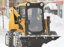 Clearing snow from the road with bulldozer in the city. Urban landscape Stock Photography