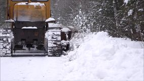 Clearing snow from the road. Crawler Tractor grader clears snow from the road. stock video footage