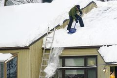 Clearing Snow from a Roof in Quebec stock photo