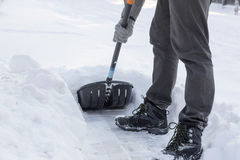 Clearing snow with a shovel from sidewalk Royalty Free Stock Images