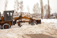 Clearingowy śnieg w Rosja Równiarka rozjaśnia sposób po ciężkiego opad śniegu Ciągnik rozjaśnia drogę w podwórzu kondygnacja fotografia stock