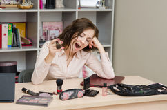 Clearly bored secretary in the office. Young woman sitting at office table, laid out on the table cosmetics Stock Photos