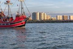 CLEARWATER FLORIDA - MAJ 05, 2015: Delfin och piratkopierar lösenfärjan i Clearwater skjuten solnedgångtid för exponering long royaltyfri fotografi