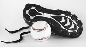 Cleat and Ball. Isolated Black and White Baseball Cleat and a baseball ball with red lacing Stock Photos