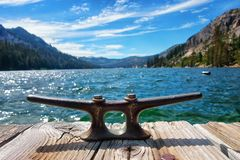 Cleat at the end of a dock at Echo Lake in the Sierras of California. Bronze cleat fastened to an old wooden boat dock on the pristine blue waters of Echo Lake Stock Photography
