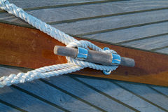 Cleat and rope on a sailboat. Cleat and rope on a wooden sailboat with teak-deck Stock Images