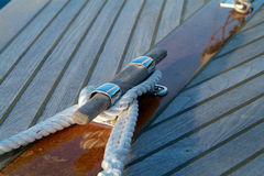 Cleat and rope on a wooden sailboat. With teak-deck Stock Images