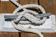 Cleat on wooden dock. With hitched rope Stock Photography