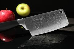 Cleaver and apples on wet surface. Cleaver and apples on wet black surface stock photos