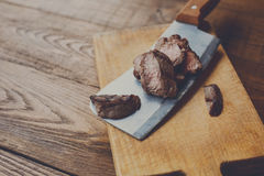Cleaver knife slicing grilled steak on meat cutting wood board. Cleaver butcher`s knife slicing grilled steak on meat cutting board on wooden background. Fresh royalty free stock photos