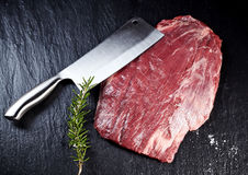 Cleaver with a lean raw shank steak. Sharp stainless steel kitchen cleaver with a lean raw shank steak and sprig of fresh rosemary on a slate counter viewed from Stock Image