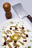 Cleaver, meat, yogurt and jam. A closeup of a dish made up of yogurt with pieces of meat and some jam in it. A pepper grinder and cleaver is placed next to the Stock Photo