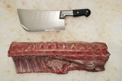 Cleaver And Raw Meat On Countertop Stock Photos