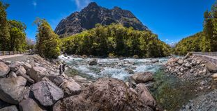 People enjoing a stopover at Falls Creek on the way to Milford S. Cleddan River, Fiordland National Park,New Zealand - December 18, 2017:  Panoramic View of Royalty Free Stock Photo