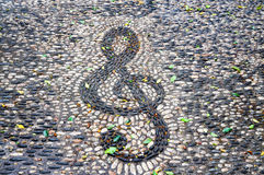 Clef Music. Clef  made of pebble stones on the pavement in a public park  in Catania, Sicily Stock Images