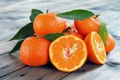 A clementina fresca cortou ao meio, em uma base de madeira Fotografia de Stock