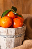 Clementine Crop. Crop of clementines in rustic keg with burlap sacking and wooden background Stock Photos