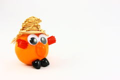 Clementine With Funny Face And Straw Hat. A fresh clementine fruit decorated to look like a humorous creature. The features are created with assorted candies and Stock Image