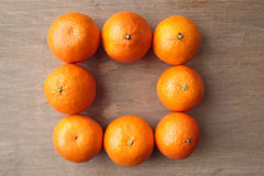 Clementine Oranges. Arranged in a square shape over wooden background.  A hybrid between a mandarin orange and a sweet orange Stock Photo