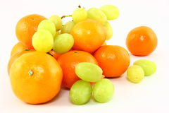 Clementines And Grapes On White. A pile of fresh orange clementines and fresh pale green grapes isolated on a white background Royalty Free Stock Images