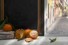 Clementines and leaves on window sill, alley Royalty Free Stock Images