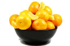 Clementines. A lots of clementines in the black bowl, fresh yellow fruits royalty free stock photography