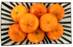 Clementines on a plate. Eight bright orange clementines on a black and white plate taken from above royalty free stock photography