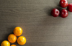 Clementines and Plums on Table. Rich colors of orange and red that makes the plums and clementines stock photography