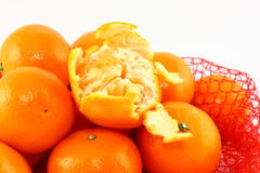 Clementines In A Red Net Close Up. A close up photo of fresh orange clementines piled in a red net bag. One fruit on top of the pile has been partially peeled Stock Image