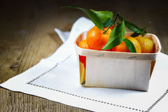 Clementines on table. Mandarin Oranges (Clementines) in a shipping box on wooden table Royalty Free Stock Photo