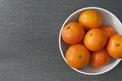 Clementines in white bowl on slate Stock Photos
