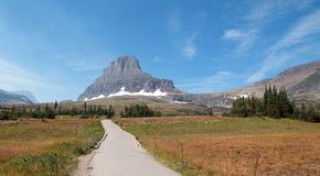 CLEMENTS MOUNTAIN TOWERING ABOVE HIDDEN LAKE HIKING TRAIL ON LOGAN PASS DURING 2017 FALL FIRES IN GLACIER NATIONAL PARK MONTANA US. CLEMENTS MOUNTAIN TOWERING stock photos