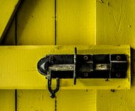 The clench of a wooden door. The object of this yellow door is used to block access to the barn. Montreal, Quebec, Canada; May 15, 2018 stock photos