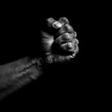 Clenched fist. On a black background royalty free stock photography