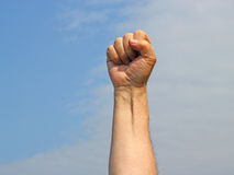 Clenched fist with a blue sky background.. Royalty Free Stock Photography