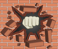 Clenched fist. Fist breaking through red brick wall Royalty Free Stock Photo
