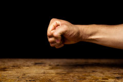 Clenched fist. Clenched fish on black background above wooden surface Royalty Free Stock Photo