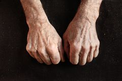 Clenched fists of old man. On black fabric Royalty Free Stock Images