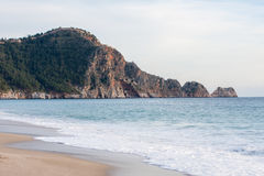 Cleopatra beach Alanya. Castle Rock of Cleopatra beach in Alanya Turkey with sea and sand on front plan and rock covered with pine forests on bacground Stock Photography