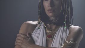 Close up of a young Cleopatra with lots of jewelry on her. Cleopatra is wearing white dress and blue makeup with a lot of jewelry with big colorful gems stock footage