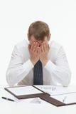 Clerck stancato che si siede alla tavola ed al closing il suo fronte immagine stock