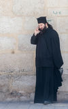 The clergyman stands and talks on his mobile phone in the old city of Jerusalem, Israel.