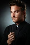 Cleric meditating with rosary. Portrait of young cleric meditating with rosary handheld, smiling royalty free stock photo