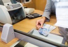 Clerk con el dinero del efectivo de los francos suizos en la oficina del banco Fotografía de archivo