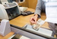 Clerk con el dinero del efectivo de los francos suizos en la oficina del banco Imagen de archivo