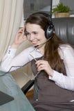 Clerk con los auriculares que se sientan en silla en oficina. Fotos de archivo libres de regalías