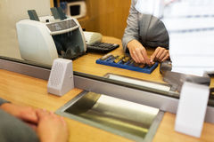 Clerk counting cash money at bank office. People, money, saving and finance concept - clerk counting coins for customer at bank office or currency exchanger Stock Photo