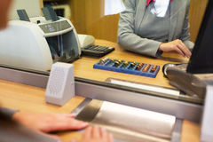 Clerk counting cash money at bank office. People, money, saving and finance concept - clerk counting coins for customer at bank office or currency exchanger Stock Photos