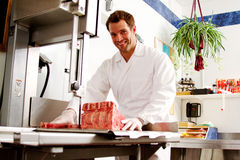Clerk cutting steaks. With saw in butcher shop Royalty Free Stock Images