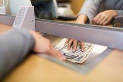 Clerk el donante del dinero del efectivo al cliente en la oficina del banco Imagenes de archivo